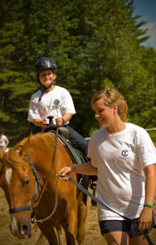 A counselor leads a camper's horse.