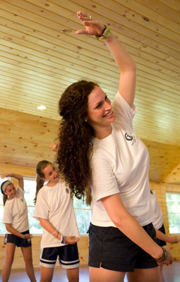 A college-age counselor teaches dancing.