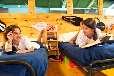 Two campers visit in their summer camp bunks.
