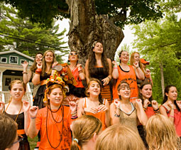 Campers dressed in black and orange sing camp songs.