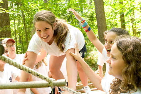 A girl climbs the ropes course with the help of her friends and fellow campers.