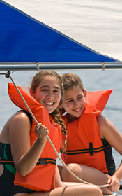 Two girls sail a boat on Tripp Lake.