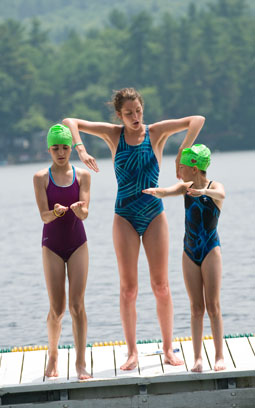 A summer camp counselor teaches swimming.