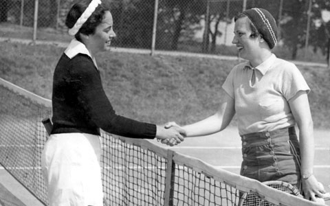 Two campers shake hands after a tennis match.