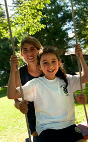 An older camper pushes a younger camper in a swing.